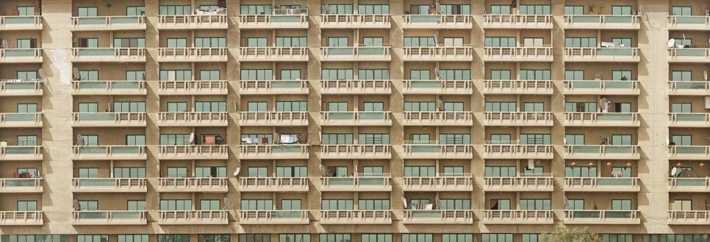 A photograph showing a facade of a large block of flats; appears to be nine columns of balconies, all almost identical but for some washing on the line.