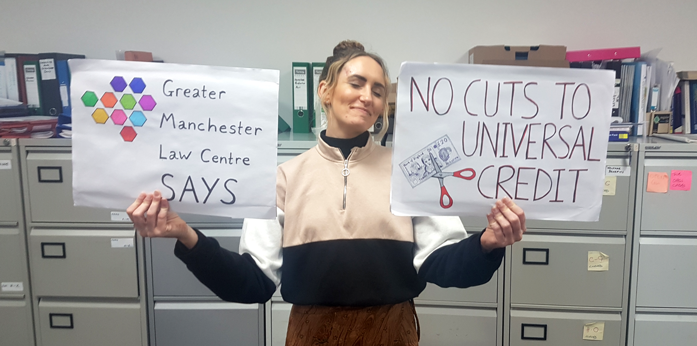 """Image showing our staff member Josie holding up two placards,one on the left that says """"Greater Manchester Law Centre Says"""" and on the right says """"No cuts to universal credit"""". Josie is smiling and the background is the GMLC office - mostly grey filing cabinets."""