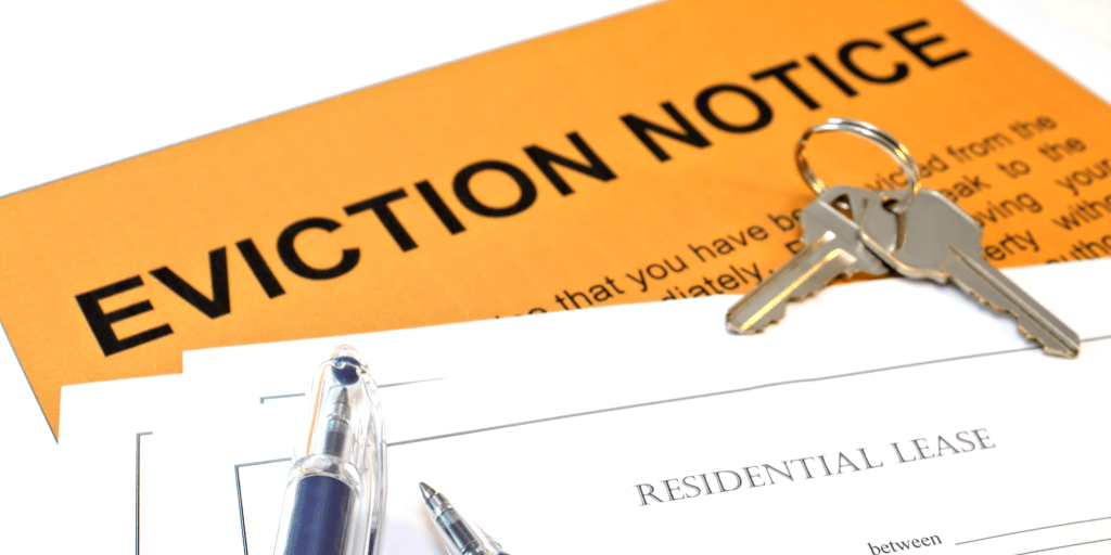 "The image shows a pen resting on an orange piece of paper that reads ""Eviction Notice""."