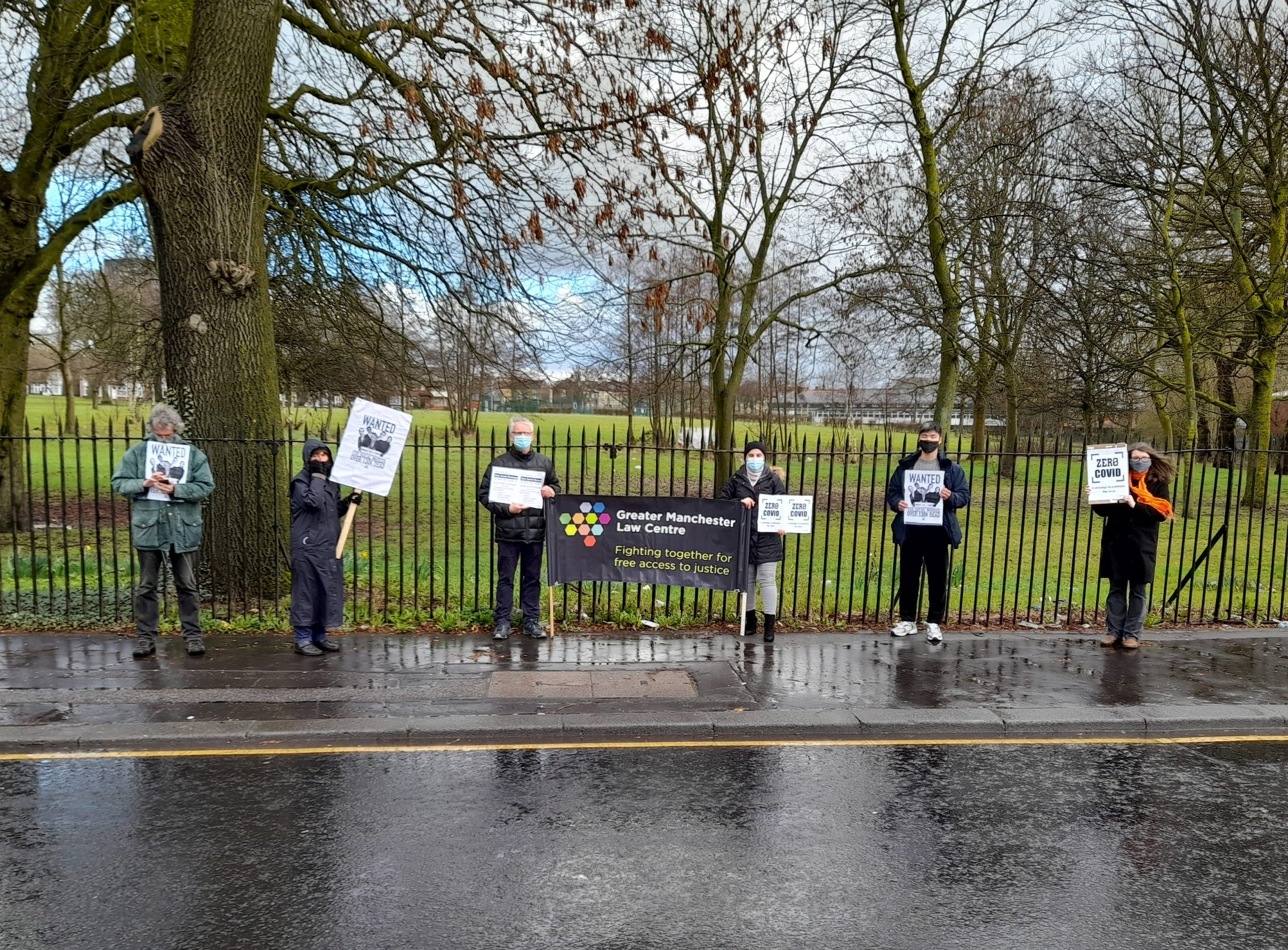 Image shows 6 people wearing masks and standing at 2m distance from one another, holding banners for Zero Covid in front of a park, with a Greater Manchester Law Centre banner in the middle.