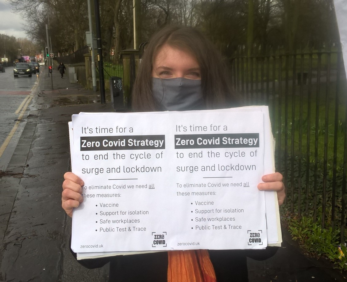 Image shows a woman, in a mask, holding up a sign that reads 'It's time for a Zero Covid strategy to end the cycle of surge and lockdown. This means vaccines, support to isolate, safe workplaces and public Test & Trace'