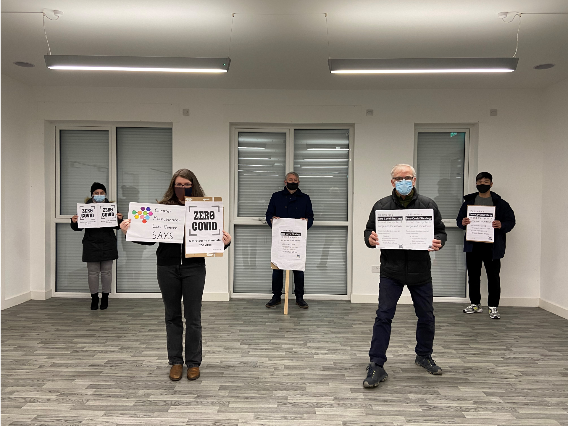 Image shows 5 people, inside a hall wearing masks and at 2m social distance, holding up Zero Covid placards.