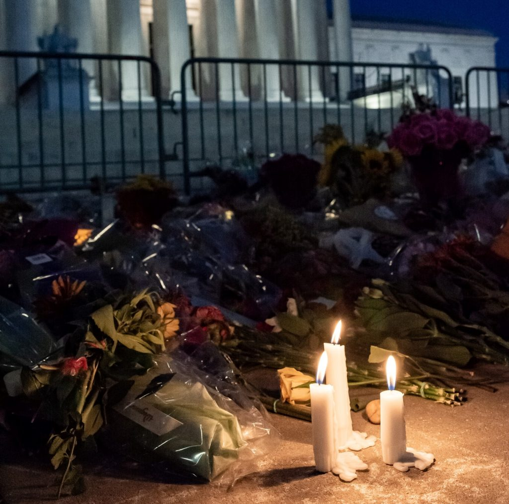 Image shows flowers and candles laid before a fence, which separates us from a large grand building, not unlike a court.