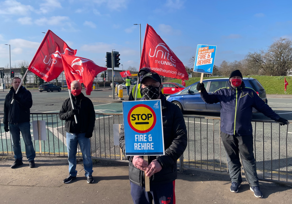 Image shows bus workers on strike at Go NorthWest holding up a sign that reads 'Stop Fire and Rehire', several people holding red Unite flags in the background.