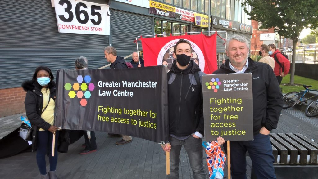 Ajibike, Cian and Jason from GMLC at a demonstration against benefits cuts holding banners.